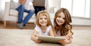 dwie dziewczynki grające na tablecie